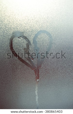 Closeup on abstract blurred love heart symbol drawn by hand on the wet frozen window glass with yellow gold sunlight background. Selective focus used. - stock photo