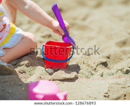 Closeup on baby girl playing with bucket and shovel on beach - stock photo
