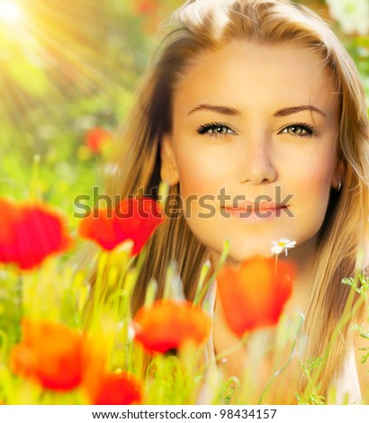 Closeup on beautiful woman face, female enjoying flower field, lovely girl at spring outdoor vacation, nice model relaxing at floral poppy garden, gorgeous model over natural bakground at sunny day - stock photo