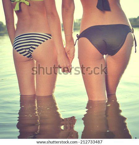 closeup on 2 beautiful young women with perfect fitnes shape buttocks having fun posing on summer water outdoors copy space background - stock photo