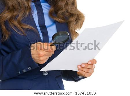 Closeup on business woman examining document using magnifying glass - stock photo
