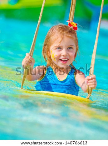Closeup on cheerful baby girl with face paint swinging on water attractions, having fun in poolside, summer vacation, happy childhood concept - stock photo