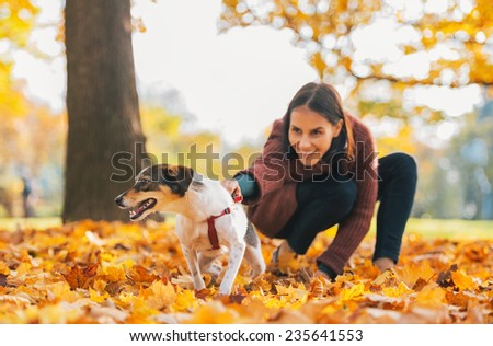 Closeup on cheerful dog and young woman holding it outdoors in autumn - stock photo