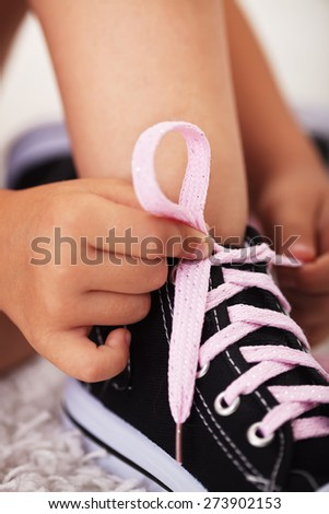 Closeup on child hands as they tie shoes - stock photo