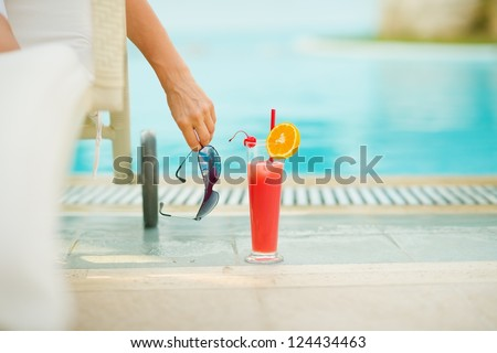 Closeup on cocktail near chaise-longue with relaxing woman - stock photo