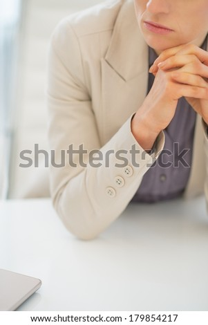 Closeup on concerned business woman sitting at desk - stock photo