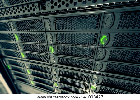 Closeup on data servers while working. Green LED lights are flashing. Image can represent cloud computing, information storage, etc. or can be the perfect technology background. - stock photo
