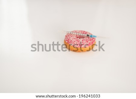 Closeup on donut and diabetes syringe on table - stock photo