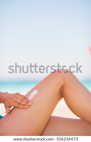 Closeup on female hand applying sun block creme on leg - stock photo