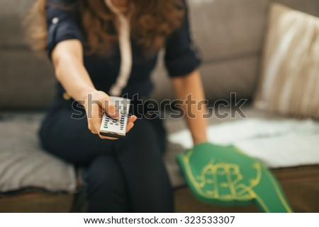 Closeup on football fan woman sitting on couch in loft apartment and watching tv. Modern lifestyle concept. - stock photo