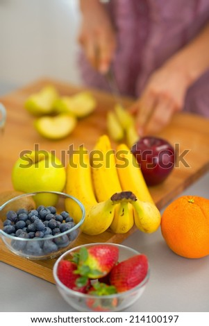 Closeup on fruits and young housewife cutting in background - stock photo
