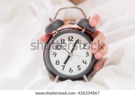 Closeup on hand reaching to turn off alarm clock. beautful fingers - stock photo