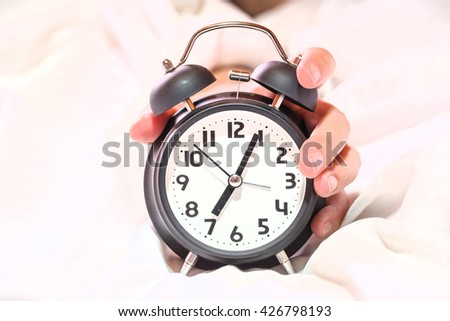 Closeup on hand reaching to turn off alarm clock.beautful fingersi - stock photo