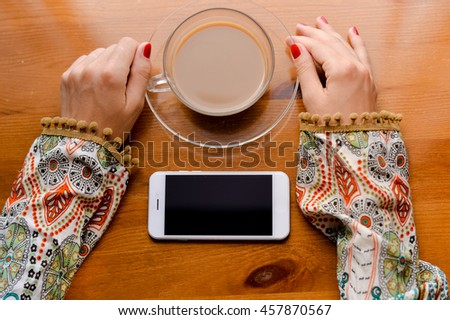 Closeup on hand using mobile smart phone, wooden desk background, mock up flat lay - stock photo