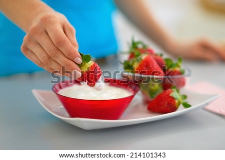 Closeup on happy young woman eating strawberry with yogurt in kitchen - stock photo