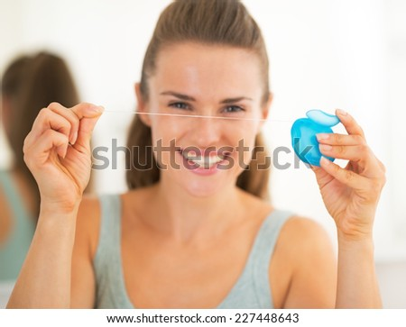 Closeup on happy young woman showing dental floss - stock photo