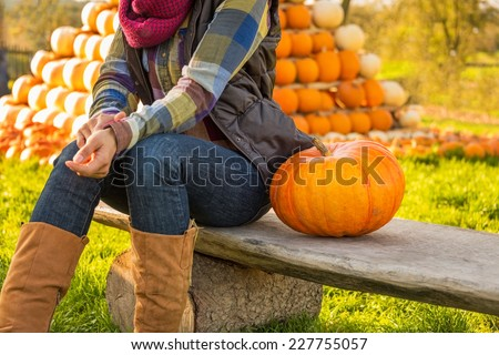 Closeup on happy young woman sitting with pumpkin in front of pumpkin piramide - stock photo