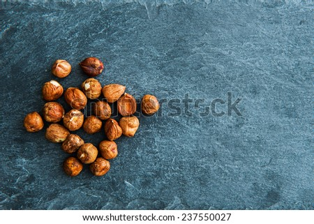 Closeup on hazelnuts on stone substrate - stock photo