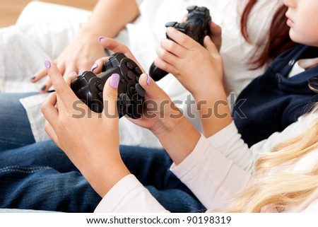 Closeup on kids hands playing console games using joystick - stock photo