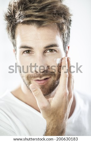 closeup on man applying cream on his face - stock photo