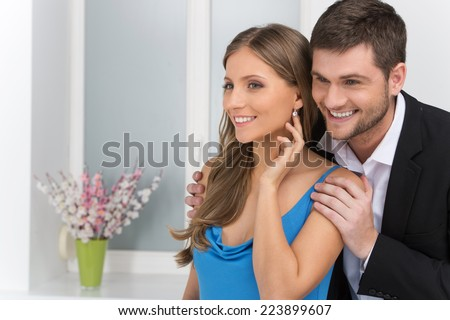 Closeup on man looking at earring on girl's ear. man standing behind woman wearing jewelry - stock photo