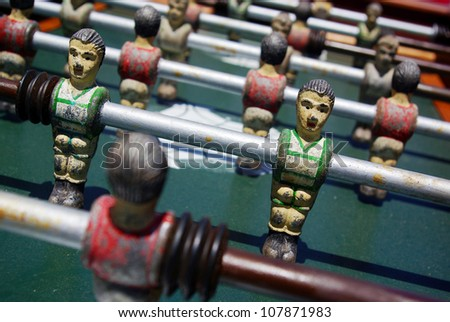 Closeup on miniature metallic ball players of a Foosball table game - stock photo