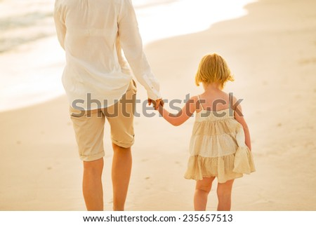 Closeup on mother and baby girl walking on beach at the evening. rear view - stock photo