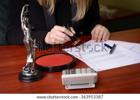 Closeup on notary hand stamping the document. Next to the notary statuette of the goddess of justice - Themis - stock photo