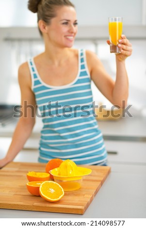 Closeup on oranges on table and young woman with glass of fresh orange juice in background - stock photo