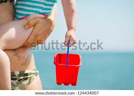 Closeup on pail in baby hand - stock photo