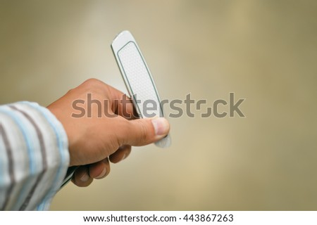 Closeup on person holding golf club in hand, shop background - stock photo