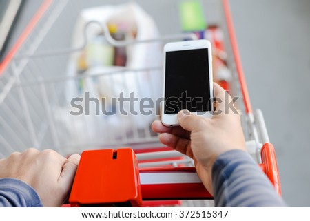 Closeup on person holding mobile phone in hand during shopping. Cart on store background - stock photo