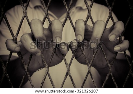 closeup on prison  hands of man in cage , color filter process - stock photo