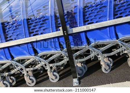 closeup on row of shopping trolleys or carts in supermarket - stock photo