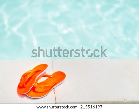 Closeup on sandals laying near swimming pool - stock photo