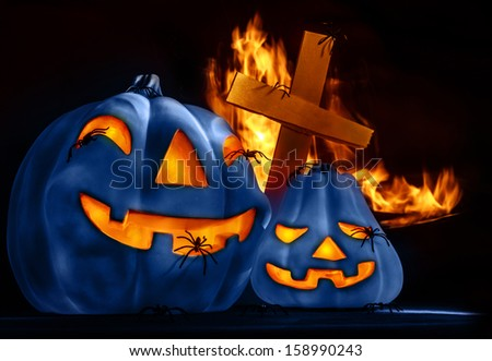 Closeup on scary Halloween decorations, eerie glowing blue carved pumpkin, eldritch spiders, cross and burning fire on graveyard, uncanny holiday night - stock photo