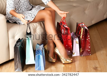 Closeup on shopping bags near woman legs. Perfect shopaholic legs with high heels. Holidays and relaxation concept