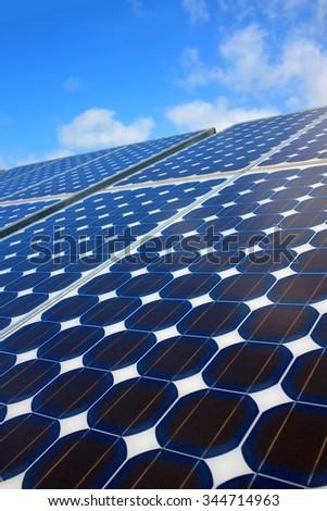 Closeup on solar panels capturing the sunlight over a blue sky - stock photo
