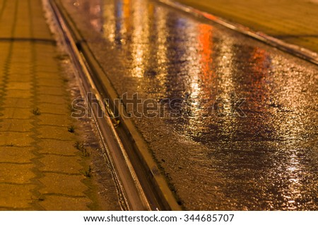 Closeup on tram rail by night, lights reflected in the wet asphalt - stock photo