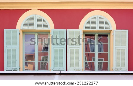 Closeup on Two Windows of the Bright Colored Facade of a Building - stock photo