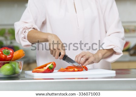 Closeup on woman cutting fresh vegetables in kitchen - stock photo