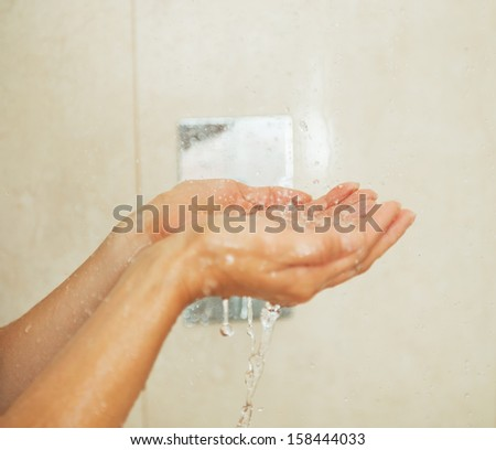 Closeup on woman hand catching water drops in shower - stock photo