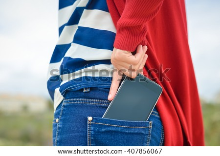 Closeup on woman hand takes out smartphone of her rear pocket of jeans on outdoors background - stock photo