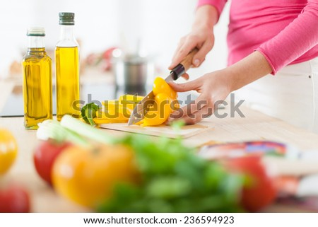 closeup on woman's hands cutting vegetables on a work surface in a kitchen - stock photo