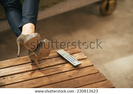Closeup on woman watching tv in loft apartment - stock photo
