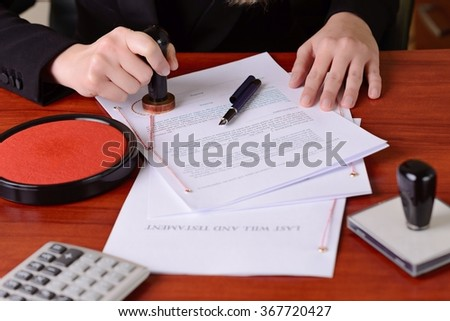 Closeup on womans notary's public hands stamping the testament and last will - stock photo