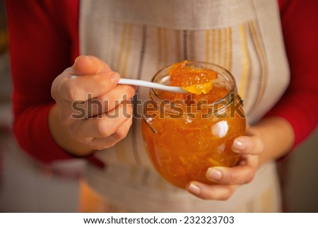 Closeup on young housewife holding homemade orange jam - stock photo