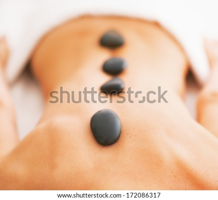 Closeup on young woman receiving hot stone massage - stock photo