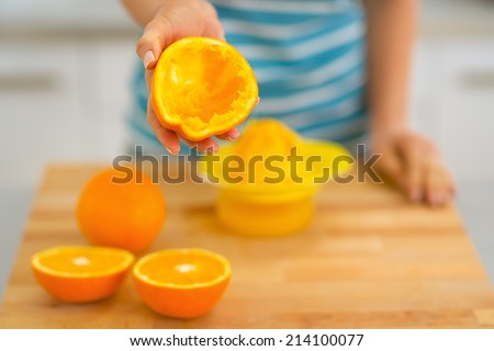 Closeup on young woman showing orange peel after squeezing juice - stock photo