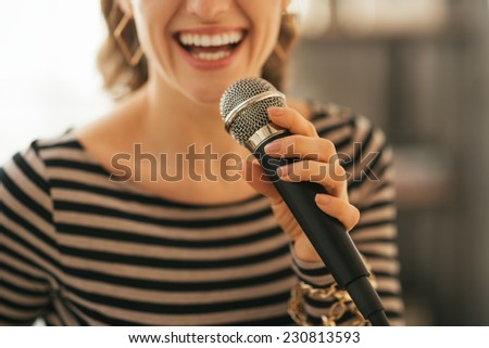 Closeup on young woman singing with microphone in loft apartment - stock photo
